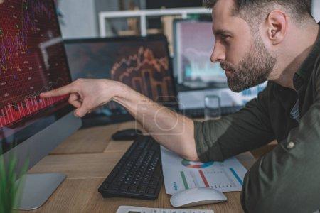 Photo pour Vue latérale d'un analyste de la sécurité de l'information pointant du doigt sur des tableaux sur un écran d'ordinateur pendant qu'il travaillait au bureau - image libre de droit