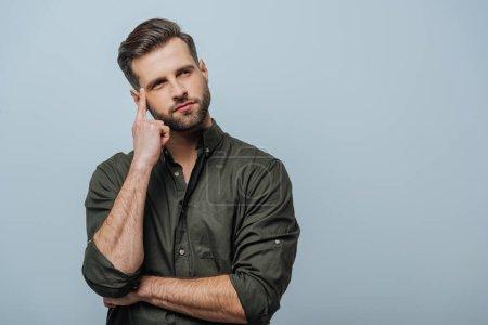 Photo pour Homme pensif avec doigt près de la tête regardant loin isolé sur gris - image libre de droit