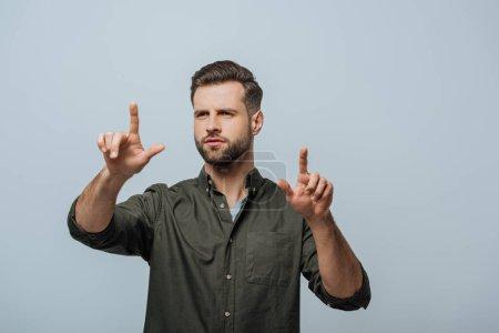 Photo pour Bel homme pointant avec les doigts isolés sur gris - image libre de droit