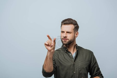 Handsome bearded man pointing with finger isolated on grey