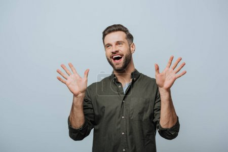 Handsome man laughing and looking away isolated on grey
