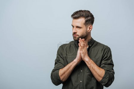Photo for Handsome bearded man with praying hands looking away isolated on grey - Royalty Free Image