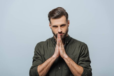 Photo for Handsome man with praying hands looking at camera isolated on grey - Royalty Free Image