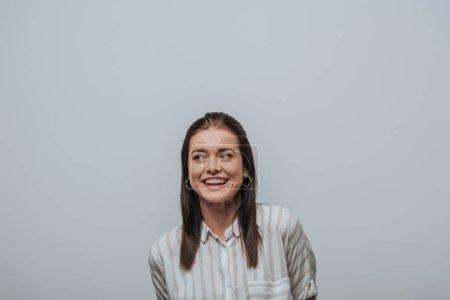 Beautiful smiling girl looking away isolated on grey