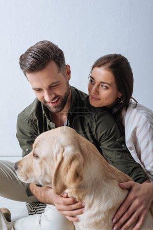 Photo pour Belle femme regardant petit ami souriant tout en caressant golden retriever sur le sol sur fond gris - image libre de droit