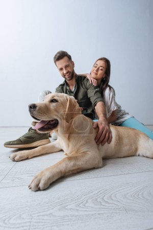Photo for Low angle view of smiling couple sitting on floor near golden retriever on grey background - Royalty Free Image