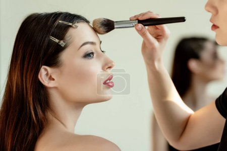 Photo for Side view of makeup artist applying face powder on beautiful model - Royalty Free Image