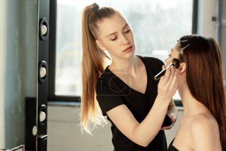Photo pour Belle maquilleuse appliquant de la poudre visage sur le modèle - image libre de droit