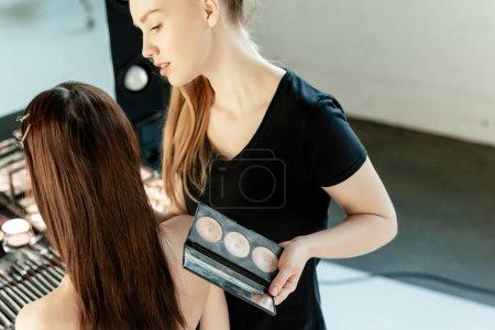 Photo pour Jeune maquilleur tenant correcteur près du modèle - image libre de droit