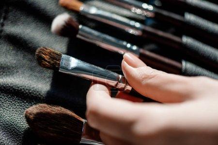 Photo pour Crochet vue d'un maquilleur prenant une brosse cosmétique - image libre de droit