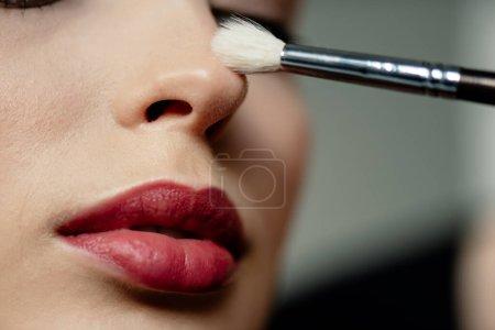 Photo pour Foyer sélectif de brosse cosmétique près de la femme avec des lèvres rouges - image libre de droit