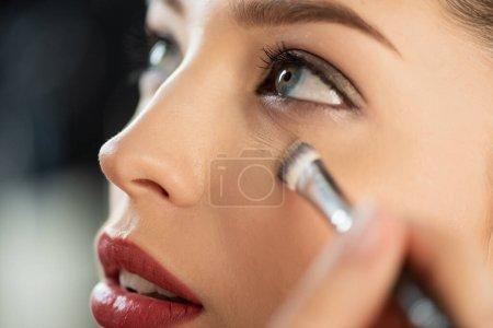 Photo pour Foyer sélectif du maquilleur appliquant correcteur sur la femme - image libre de droit