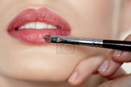 Photo pour Vue recadrée du maquilleur appliquant rouge à lèvres sur fille - image libre de droit