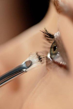 Photo pour Gros plan de la brosse cosmétique près de l'oeil du modèle - image libre de droit