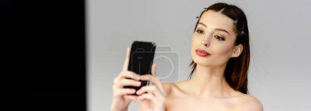 Photo pour Plan panoramique de belle femme prenant selfie sur gris et noir - image libre de droit