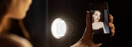 Photo for Panoramic shot of woman taking selfie in photo studio - Royalty Free Image