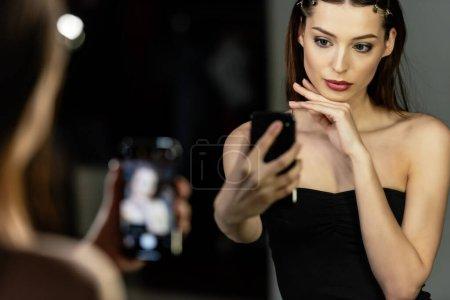 selective focus of attractive woman taking selfie in photo studio