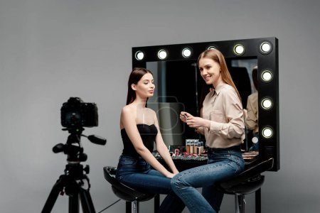 Photo for Selective focus of happy makeup artist holding cosmetic brush and lip gloss near model and digital camera isolated on grey - Royalty Free Image