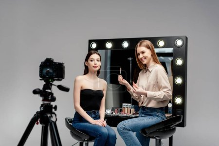 selective focus of happy makeup artist holding lip gloss near model and digital camera isolated on grey