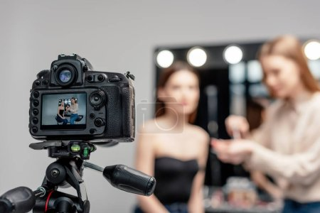 selective focus of digital camera with makeup artist holding lip gloss near model on screen isolated on grey