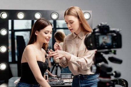 Photo pour Foyer sélectif du modèle souriant près du maquilleur tenant gloss lèvre près de l'appareil photo numérique isolé sur gris - image libre de droit