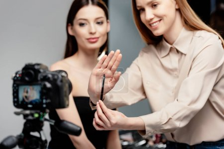Photo for Selective focus of happy makeup artist holding cosmetic brush near beautiful model and digital camera isolated on grey - Royalty Free Image