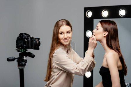 Photo pour Foyer sélectif du maquilleur heureux appliquer brillant à lèvres sur les lèvres du modèle attrayant et en regardant appareil photo numérique isolé sur gris - image libre de droit