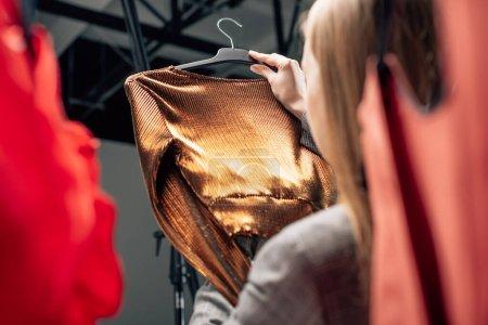 Photo pour Foyer sélectif du styliste tenant chemisier tendance sur cintre - image libre de droit