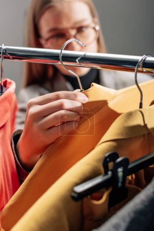 Photo for Selective focus of stylist taking hanger with fashionable clothing - Royalty Free Image