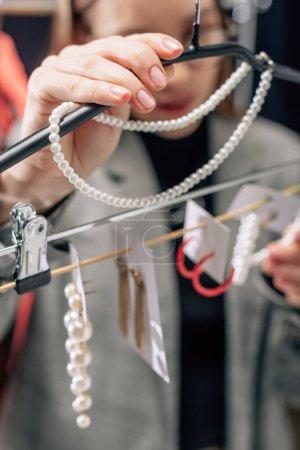 Photo pour Foyer sélectif de styliste touchant collier de perles près des boucles d'oreilles - image libre de droit