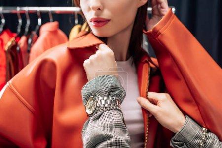 Photo pour Vue recadrée du styliste touchant veste sur le modèle - image libre de droit