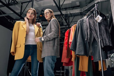 Photo for Stylist in glasses standing with trendy model in photo studio - Royalty Free Image