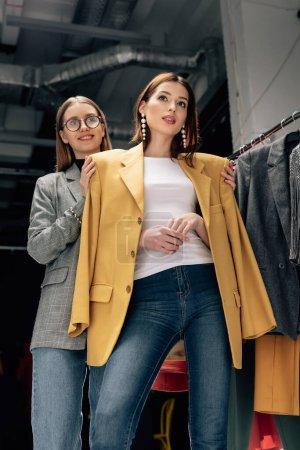 Photo pour Heureux styliste dans des lunettes debout avec modèle à la mode dans le studio photo - image libre de droit
