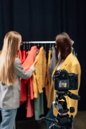 Photo for Selective focus of digital camera with stylist touching trendy clothing near model on screen - Royalty Free Image