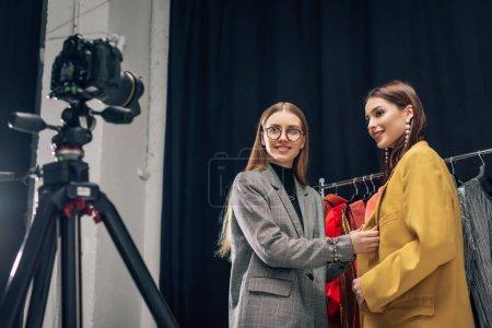 Photo pour Foyer sélectif de styliste heureux dans des lunettes touchant veste sur le modèle près de l'appareil photo numérique - image libre de droit