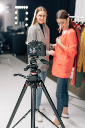 Photo for Selective focus of digital camera with happy stylist standing with trendy model on screen - Royalty Free Image