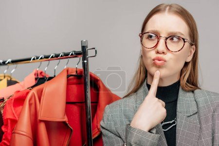 Photo for Pensive stylist in glasses touching face while thinking near trendy clothing isolated on grey - Royalty Free Image