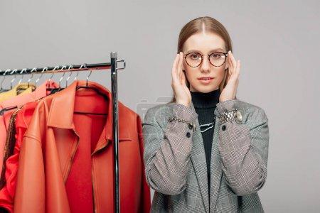 Photo pour Jeune styliste touchant lunettes près de vêtements à la mode isolé sur gris - image libre de droit