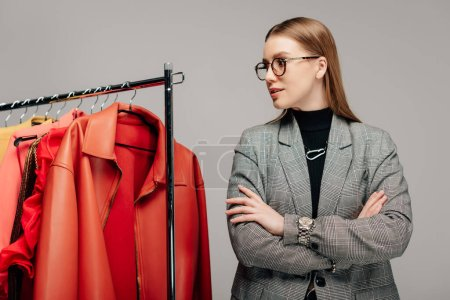 Photo for Young stylist in glasses standing with crossed arms near trendy clothing isolated on grey - Royalty Free Image