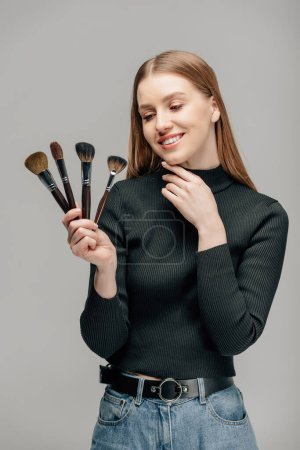 happy makeup artist holding cosmetic brushes isolated on grey