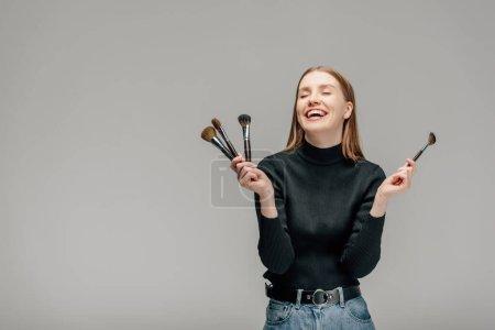 Photo pour Heureux maquilleur tenant ensemble brosse de maquillage isolé sur gris - image libre de droit