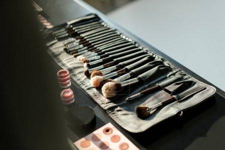 Photo pour Mise au point sélective du pinceau de maquillage près des baumes à lèvres et des ombres à paupières - image libre de droit