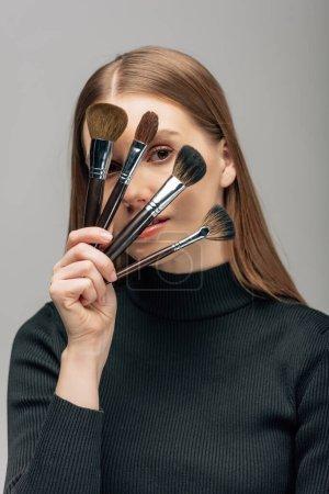 Photo pour Jeune maquilleur couvrant le visage de brosses cosmétiques isolées sur gris - image libre de droit