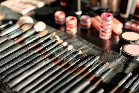 Photo pour Mise au point sélective de la brosse de maquillage près des baumes à lèvres - image libre de droit