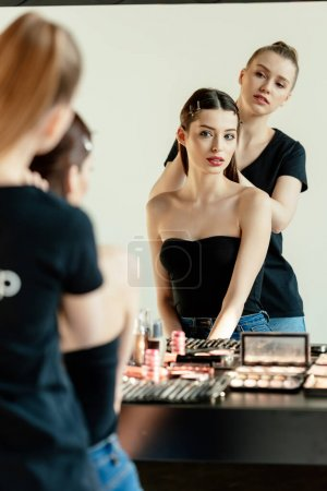 selective focus of make up artist near model and decorative cosmetics