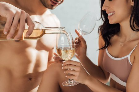 Photo for Cropped view of man pouring wine and girl smiling and holding glasses - Royalty Free Image