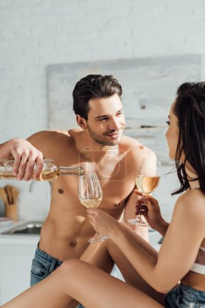 Photo for Man smiling, pouring wine and looking at girlfriend with glasses in kitchen - Royalty Free Image