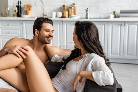 Photo for Couple looking at each other and smiling on sofa in kitchen - Royalty Free Image