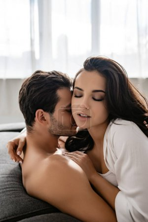 Hot girlfriend with closed eyes and boyfriend hugging on sofa