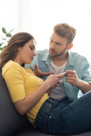 Photo pour Homme agressif pointant avec la main tout en petite amie en utilisant un smartphone sur le canapé - image libre de droit